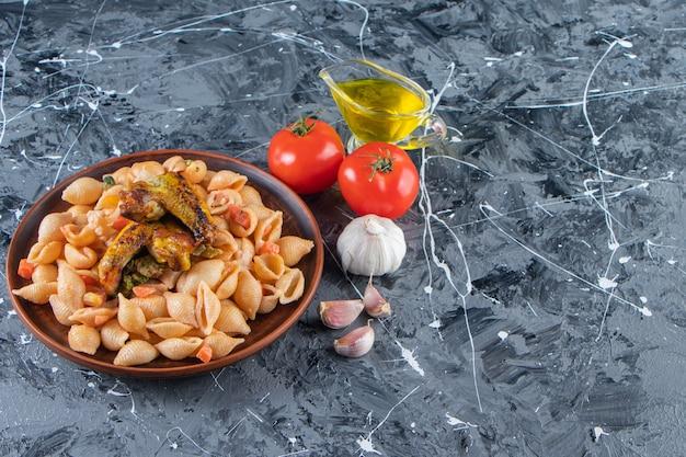 Drewniany talerz smaczny makaron z muszelkami ze skrzydełkiem kurczaka na marmurowej powierzchni.