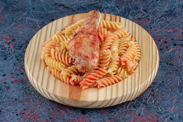 Drewniany talerz spiralnego makaronu z mięsem z nogi kurczaka