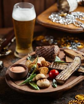 Drewniany talerz steku wołowego z grillowanym bakłażanem, ziemniakami, grzybami i sosem