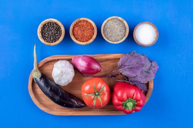 Drewniany talerz świeżych dojrzałych warzyw z różnymi przyprawami