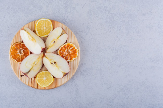Drewniany talerz świeżych jabłek i plasterków cytryny na kamiennym stole.