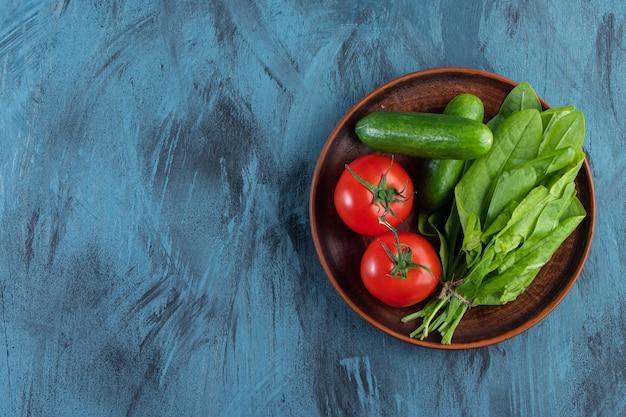 Drewniany talerz świeżych pomidorów, ogórków i zieleni na niebieskim tle.