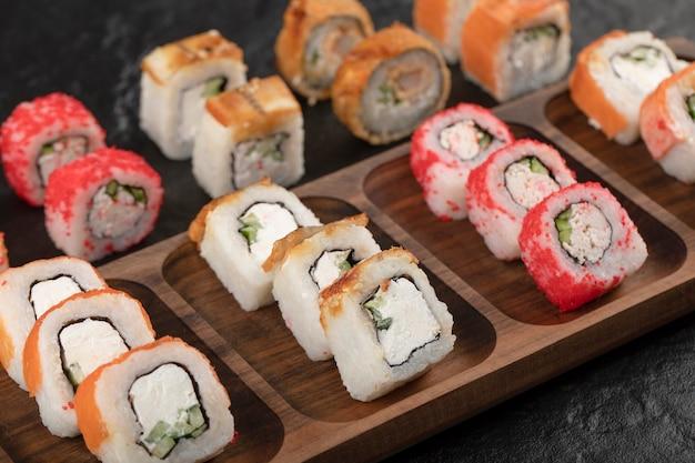 Drewniany talerz tradycyjnych rolek sushi na czarnym stole
