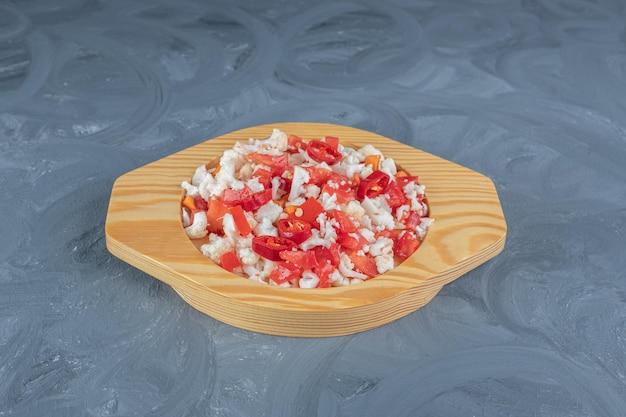 Drewniany talerz wypełniony zdrową porcją sałatki z kalafiora i papryki na marmurowym stole.