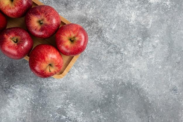 Drewniany talerz z błyszczącymi czerwonymi jabłkami na marmurowym stole.