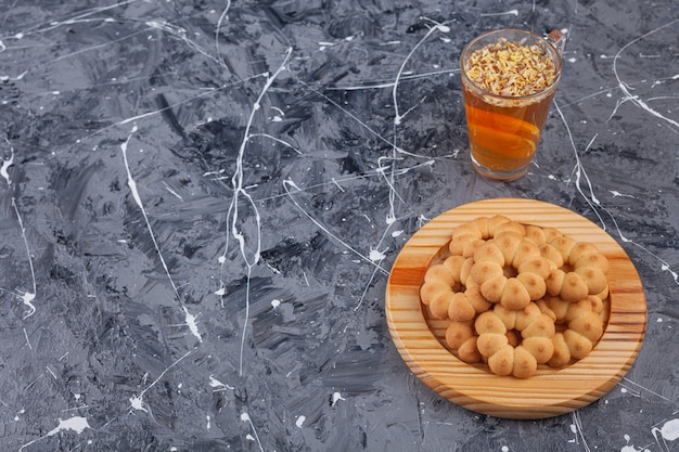 Drewniany talerz z ciasteczkami w kształcie słodkich kwiatków i filiżanką herbaty na marmurze.