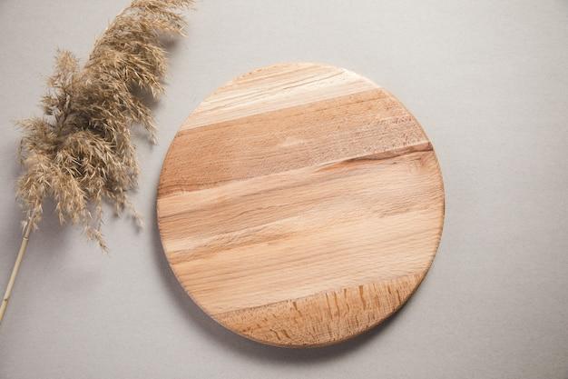 Drewniany talerz z dekoracyjną trawą na stole