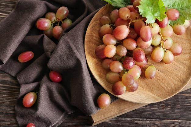 Drewniany talerz z dojrzałymi winogronami na stole