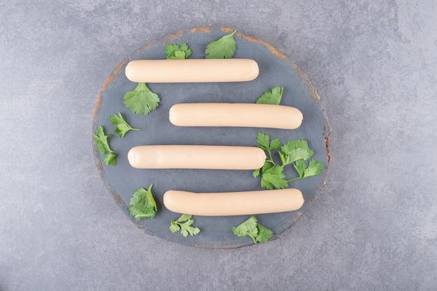 Drewniany talerz z gotowanymi kiełbasami i natką pietruszki