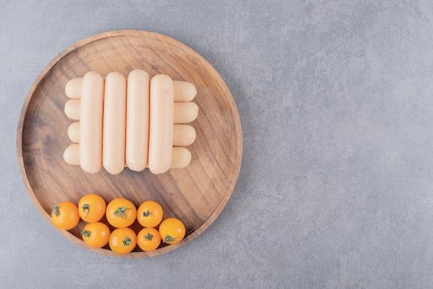 Drewniany talerz z gotowanymi kiełbasami i pomidorkami cherry.