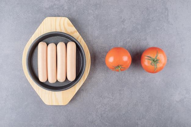 Drewniany talerz z gotowanymi kiełbasami i świeżymi czerwonymi pomidorami.