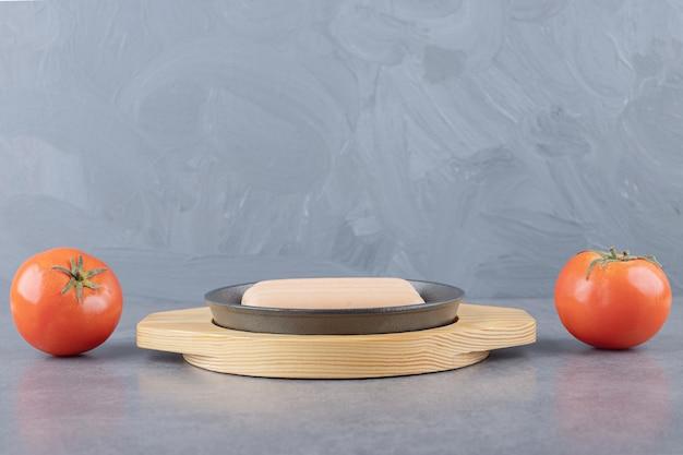 Drewniany talerz z gotowanymi kiełbasami i świeżymi czerwonymi pomidorami