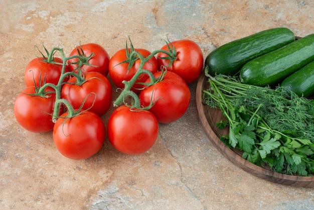 Drewniany talerz z ogórkami, zieleniną i pomidorami.