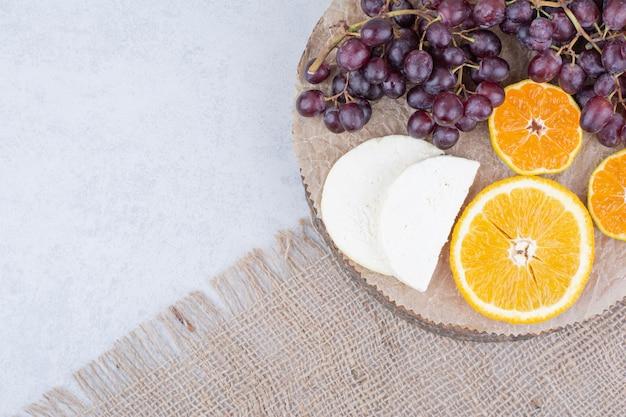 Drewniany talerz z pokrojonym serem i owocami. zdjęcie wysokiej jakości