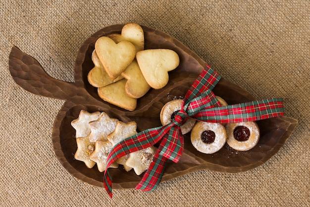 Drewniany talerz z różnymi ciastkami na stole