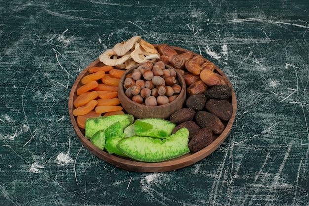 Drewniany talerz z suszonymi owocami na marmurowej powierzchni