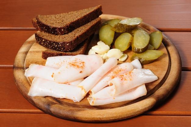Drewniany talerz z wędzonym boczkiem, marynatami i chlebem żytnim