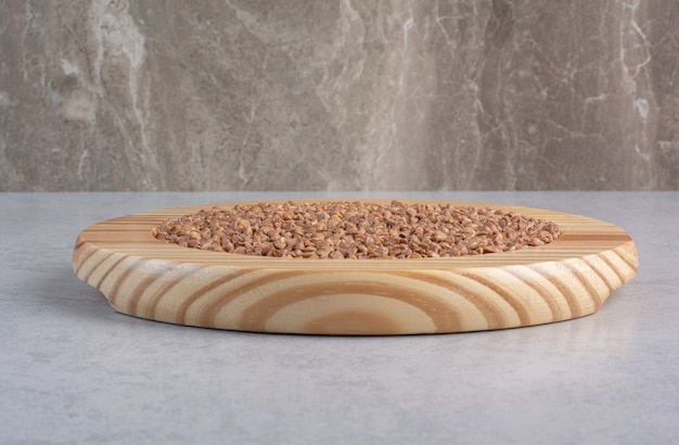 Drewniany talerz ze stertą ryżu długoziarnistego na marmurze.