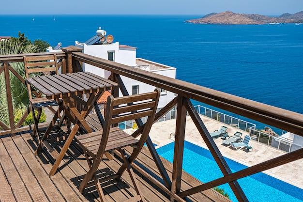 Drewniany taras willi wakacyjnej lub hotelu ze stołem z dwoma krzesłami i widokiem na morze