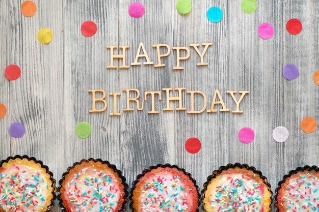 """Drewniany tekst """"happy birthday"""" z konfetti papierowymi i małymi ciastkami papugowymi z posypanym cukrem kolorowym"""