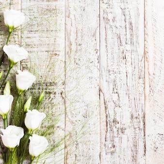 Drewniany tło z bukietem biali kwiaty
