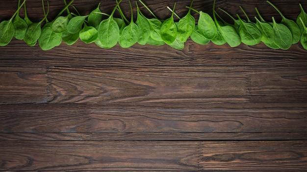 Drewniany tło z dziecko szpinakiem opuszcza. skopiuj miejsce koncepcja zdrowego odżywiania