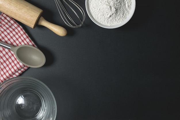 Drewniany wałek do ciasta, filiżanka mąki i trzepaczka na czarnym stole