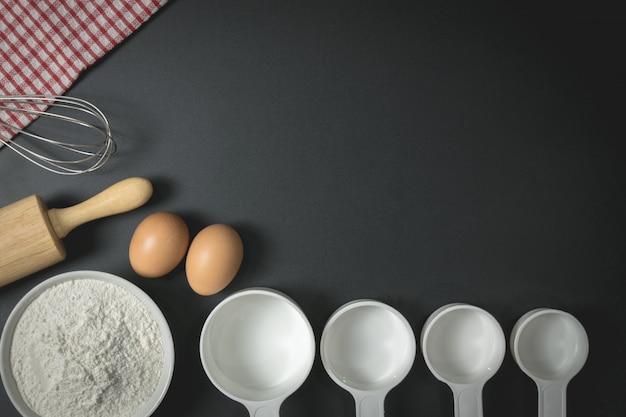 Drewniany wałek do ciasta, filiżanka mąki, jajka i trzepaczka na czarnym stole