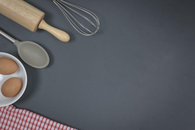 Drewniany wałek do ciasta i trzepaczka na czarnym stole z jajkami