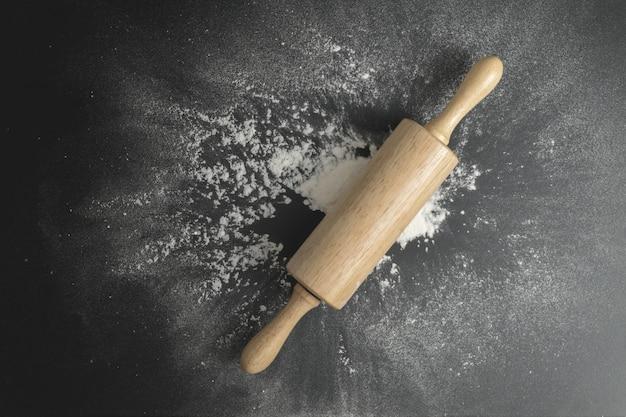 Drewniany wałek do ciasta na czarnym stole z mąką