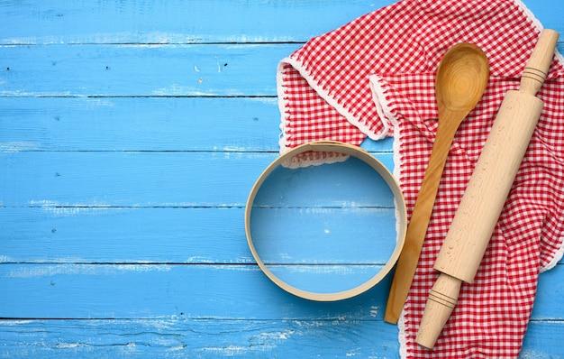 Drewniany wałek do ciasta, okrągłe drewniane sito na niebieskim tle z czerwoną serwetką, widok z góry