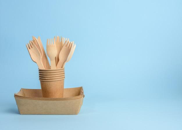 Drewniany widelec i brązowy papierowy kubek na niebieskim tle. koncepcja odrzucenia plastiku, zero odpadów, miejsce na kopię