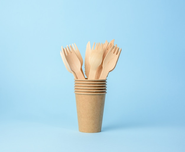 Drewniany widelec i brązowy papierowy kubek na niebieskim tle. koncepcja odrzucenia tworzyw sztucznych, zero odpadów, z bliska