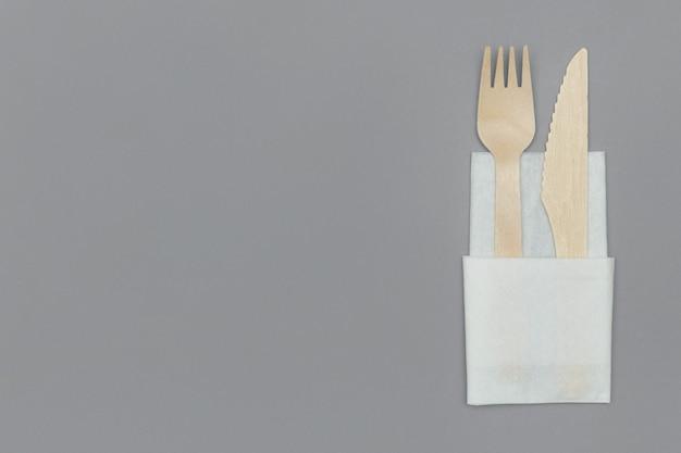 Drewniany widelec i nóż w białej serwetce na szarym tle, widok z góry. ekologiczna jednorazowa zastawa stołowa z naturalnego materiału. koncepcja ekologiczna.