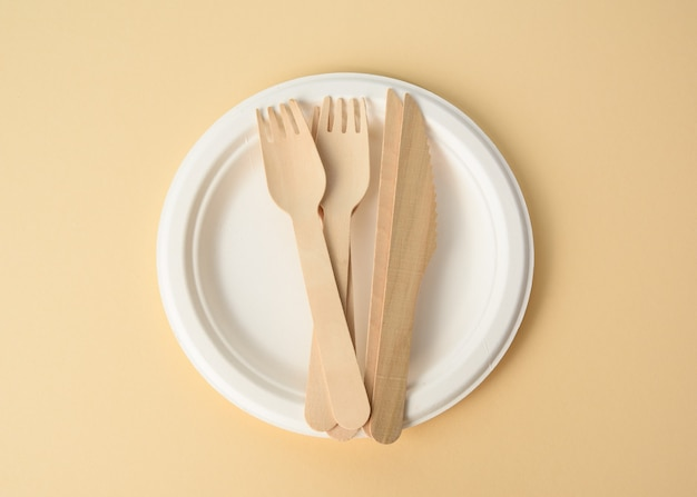 Drewniany widelec i pusty biały okrągły brązowy jednorazowy talerz wykonany z materiałów pochodzących z recyklingu na brązowym tle, widok z góry. koncepcja braku śmieci nienadających się do recyklingu, odrzucenie plastiku, widok z góry
