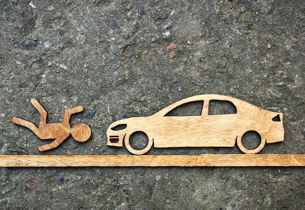 Drewniany zabawkarski mały mężczyzna i samochód na kamiennym tle. pojęcie wypadku samochodowego z mężczyzną