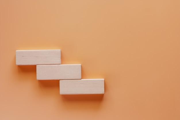 Drewniany zabawkarski schody na beżowym koloru tle dla kroka bramkowy sukcesu pojęcie