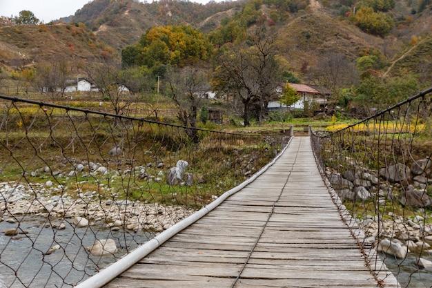 Drewniany zawieszenie most nad rzeką w górach