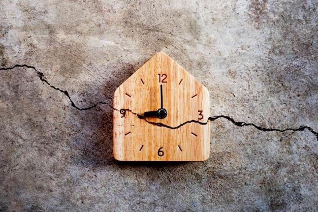 Drewniany zegar na pękniętej ścianie cementowej. widok z góry
