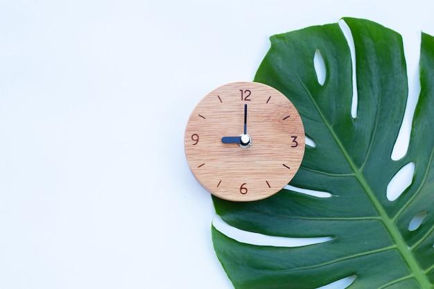 Drewniany Zegar Na Zielonych Liściach Premium Zdjęcia