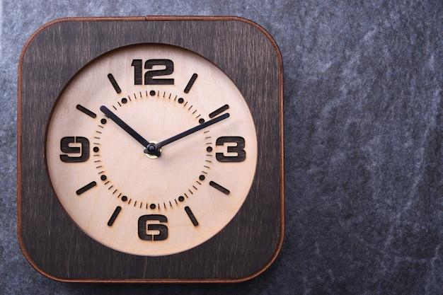 Drewniany zegar robić w ręce na drewnianym tle. zbliżenie. miejsce na tekst.