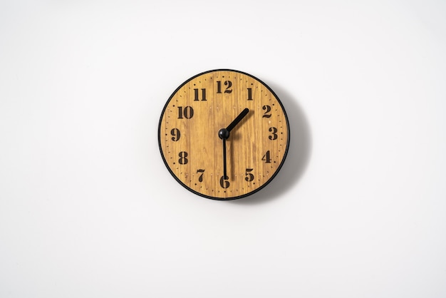 Drewniany zegar ścienny do biura z białą tarczą na białej ścianie. zegar ścienny na białym tle, widok z góry.