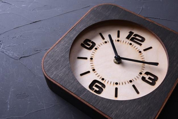 Drewniany zegar wykonany w ręku na drewnianym stole. zbliżenie. miejsce na tekst.