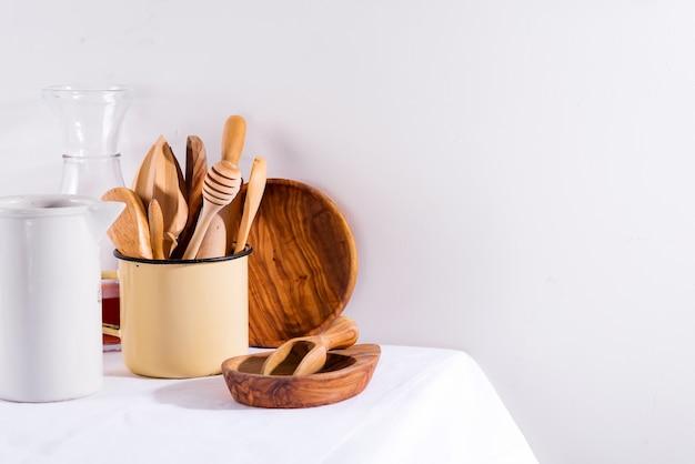 Drewniany zestaw naczyń kuchennych w żelaznej filiżance z drewnianymi talerzami na białym stole tekstylnym. urządzenia kuchenne zero marnowania