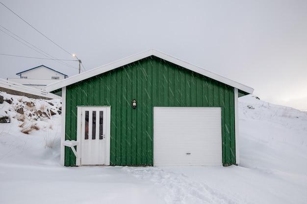 Drewniany zielony dom ze śniegiem pokrytym śniegiem w zimie w skandynawii