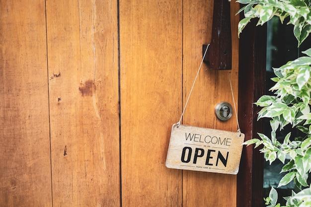 """Drewniany znak z napisem: """"jesteśmy otwarci, proszę wejść"""" powiesić na zabytkowych drewnianych drzwiach wejściowych kawiarni i restauracji. fotografia z miejsca kopiowania i tła."""