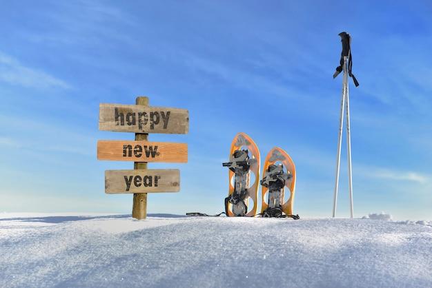 Drewniany znak z tekstem szczęśliwego nowego roku w śniegu obok rakiet śnieżnych i kijów narciarskich