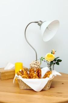 Drewnianych stołowych wypiekowych babeczek lampowego żółtego białego tła koszykowych świeżych róż pieluch kuchnia