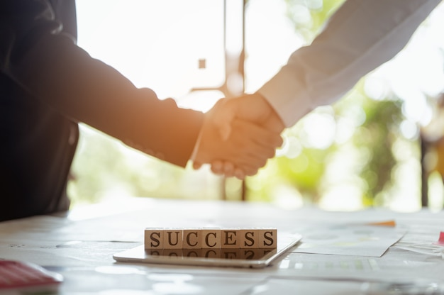 Drewno blokuje sukces słowa, uścisk dłoni na sukces.