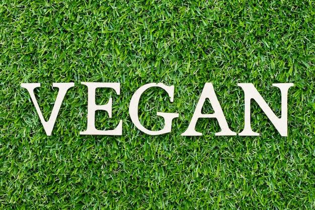"""Drewno litera w słowie """"wegańskie"""" na zielonej trawie"""